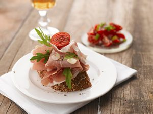 Parma ham sandwich with tomato on a white plate. Wooden table. Shallow focus, vibrant color.